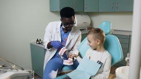 Piccolo paziente maschio che impara circa le cure odontoiatriche con il giovane dentista africano nell'ufficio del dentista stock footage