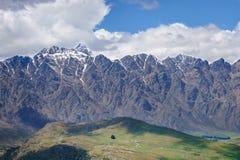 Piccolo percorso sopra una collina verde alle montagne fotografia stock