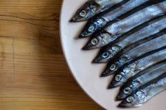 Piccolo pesce d'argento in un piatto beige su una tavola di legno, fine su fotografia stock