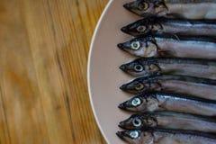 Piccolo pesce d'argento in un piatto beige su una tavola di legno, fine su immagine stock