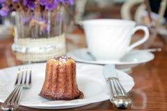 Piccolo pezzo di servire del canele in un piatto sulla tavola nel negozio del tè Immagine Stock