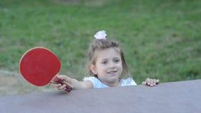 Piccolo ping-pong felice affascinante dei giochi da bambini della ragazza sulla via stock footage