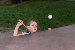 Piccolo ping-pong felice affascinante dei giochi da bambini della ragazza sulla via immagine stock libera da diritti