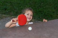Piccolo ping-pong felice affascinante dei giochi da bambini della ragazza sulla via fotografie stock libere da diritti