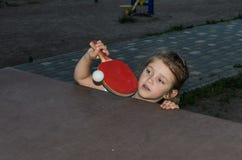 Piccolo ping-pong felice affascinante dei giochi da bambini della ragazza sulla via immagini stock