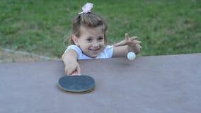 Piccolo ping-pong felice affascinante dei giochi da bambini della ragazza sulla via video d archivio