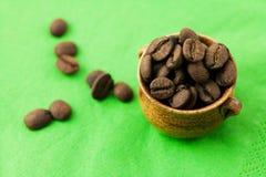 Piccolo POT dei chicchi di caffè sulla materia verde Fotografia Stock