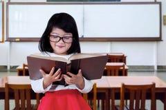Piccolo principiante che legge un libro nella classe Fotografia Stock