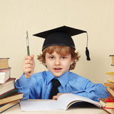 Piccolo professore in cappello accademico con la penna della rarità fra i vecchi libri Fotografia Stock Libera da Diritti