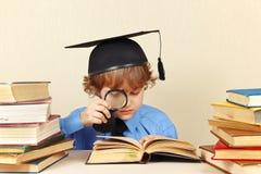 Piccolo professore nella lettura accademica del cappello libri vecchi con la lente d'ingrandimento Fotografia Stock