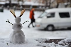 Piccolo pupazzo di neve che sta sulla veranda Immagine Stock