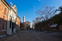 Piccolo quadrato all'isola di Murano a Venezia, con il faro nel fondo Fotografie Stock Libere da Diritti