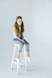 Piccolo ragazza alla moda di ribaltamento che si siede sulla sedia immagini stock libere da diritti