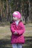 Piccolo ragazza arrabbiata di ribaltamento che sta da solo in primavera foresta Fotografie Stock Libere da Diritti