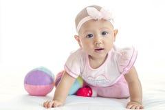 Piccolo ragazza asiatica del bambino 7 mesi con il vestito rosa che esamina macchina fotografica sul letto bianco fotografia stock libera da diritti