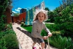 Piccolo ragazza bionda allegra che guida un motorino sui percorsi pavimentati un giorno di estate soleggiato fotografia stock libera da diritti