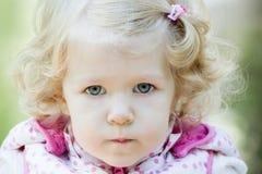 Piccolo ragazza bionda dei capelli ricci con le labbra increspate fotografia stock