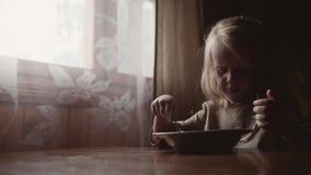 Piccolo ragazza bionda mangiare porridge vicino alla finestra archivi video