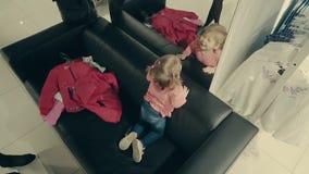 Piccolo ragazza del bambino in un negozio di vestiti si siede sullo strato davanti ad uno specchio archivi video