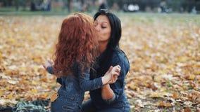Piccolo ragazza della testarossa con la sua mamma passa il tempo nel parco di autunno Essi che giocano, huging e divertiresi stock footage