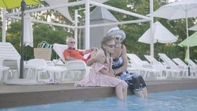 Piccolo ragazza divertente con le trecce e la donna matura che si siedono sull'orlo dello stagno con i loro piedi nell'attimo del stock footage