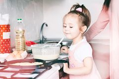 Piccolo ragazza dolce ed i suoi pancake della frittura della madre al carnevale russo tradizionale Maslenitsa Shrovetide di festa immagine stock
