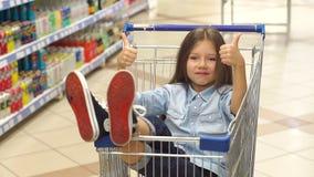 Piccolo ragazza felice si siede in un carretto della drogheria in un supermercato e mostra il suo pollice su stock footage