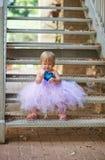 Piccolo ragazza graziosa che si siede sulle scale fotografie stock