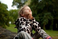 Piccolo ragazza riccia prega la seduta su un recinto di pietra Resto nel villaggio Preghiera al dio Vacanze estive fotografie stock libere da diritti