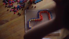 Piccolo ragazza sveglia che gioca con il mosaico variopinto stock footage