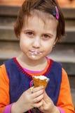 Piccolo ragazza sveglia del bambino che mangia il gelato Alimento, dessert, infanzia felice, concetto di disattenzione immagini stock libere da diritti