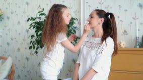 Piccolo ragazza sveglia dipinge le labbra della madre con rossetto, movimento lento stock footage
