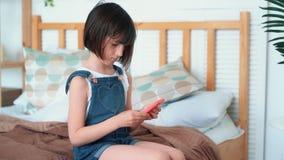 Piccolo ragazza sveglia si siede sul letto, utilizza lo smartphone per gioca, movimento lento stock footage