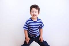 Piccolo ragazzo adorabile che sorride e che posa, tiro dello studio su bianco Emo immagini stock