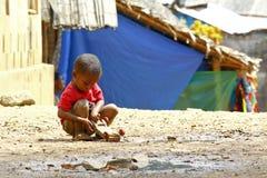 Piccolo ragazzo africano, all'aperto, giocante con un'automobile Immagine Stock