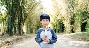 Piccolo ragazzo asiatico che cammina con il giocattolo del generatore eolico sulla strada di bambù del tunnel fotografia stock libera da diritti