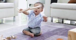 Piccolo ragazzo asiatico che gioca da solo a casa video d archivio
