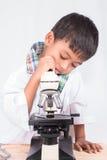 Piccolo ragazzo asiatico dello studente che lavora con il microscopio Fotografia Stock
