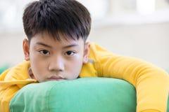 Piccolo ragazzo asiatico, perso nei pensieri e triste Fotografia Stock