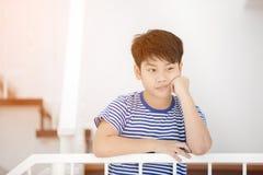 Piccolo ragazzo asiatico, perso nei pensieri e triste Immagini Stock