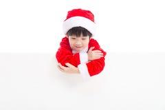 Piccolo ragazzo asiatico in uniforme di Santa Claus con un'insegna vuota Immagini Stock Libere da Diritti
