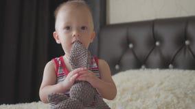 Piccolo ragazzo bello abbraccia un coniglio della peluche a casa, dell'interno Piccolo neonato che gioca con il giocattolo video d archivio