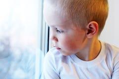 Piccolo ragazzo biondo adorabile del bambino che si siede vicino alla finestra, così triste Fotografia Stock