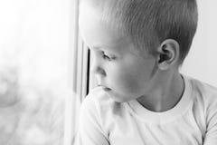 Piccolo ragazzo biondo adorabile del bambino che si siede vicino alla finestra, così triste Fotografia Stock Libera da Diritti
