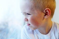 Piccolo ragazzo biondo adorabile del bambino che si siede vicino alla finestra, così triste Fotografie Stock