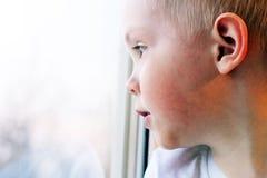 Piccolo ragazzo biondo adorabile del bambino che si siede vicino alla finestra, così triste Fotografie Stock Libere da Diritti