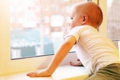 Piccolo ragazzo biondo adorabile del bambino che si siede vicino alla finestra, così triste Immagine Stock