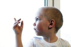 Piccolo ragazzo biondo adorabile del bambino che si siede vicino alla finestra, mano del bambino Immagini Stock Libere da Diritti