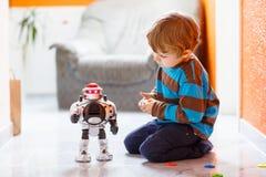 Piccolo ragazzo biondo che gioca con il giocattolo del robot a casa, dell'interno Fotografie Stock