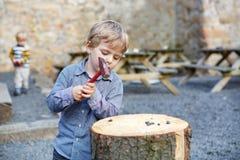 Piccolo ragazzo biondo che gioca con il martello all'aperto con il fratello. Fotografie Stock